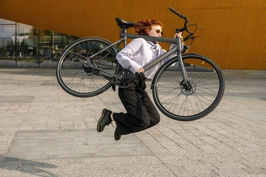 Woman jumps in the air holding an Equal e-bike